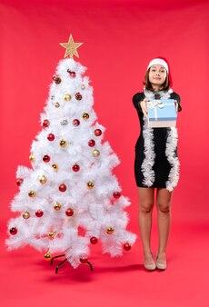 クリスマスツリーの近くに立っているサンタクロースの帽子と黒いドレスを着た幸せな女の子とクリスマス気分の上面図