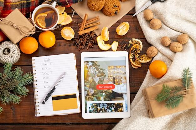 Вид сверху рождественского промо в планшете, пластиковой карточке, ручке в рождественском списке в окружении других праздничных вещей на столе