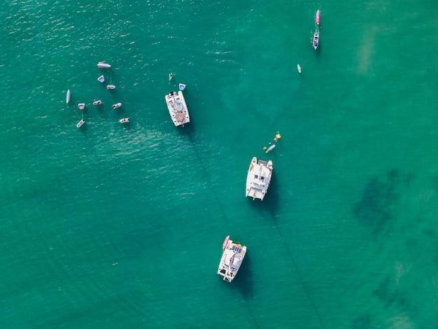 Вид сверху на парусную яхту с водными лыжами и лодкой-бананом на бирюзовом тропическом море