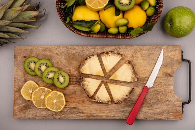 灰色の背景にナイフで木製のキッチンボードにキウイレモンとパイナップルのスライスとバケツにキウイキンカンとレモンなどの黄色と緑の果物の上面図