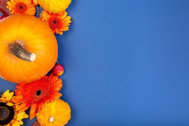 コピースペースと青い表面に黄色とオレンジ色の花とカボチャの上面図
