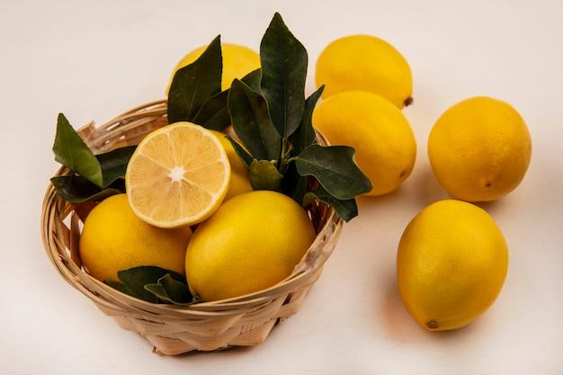흰 벽에 양동이에 노란색과 둥근 레몬의 상위 뷰