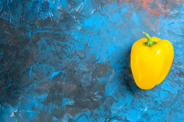 Вид сверху желтого болгарского перца на синей поверхности