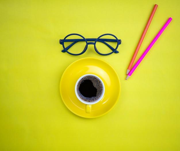 黄色の紙の背景に先生のメガネとカラフルな鉛筆と黄色のコーヒーカップの上面図