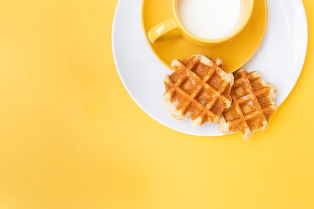 白い皿と黄色の背景に黄色のカップと牛乳とワッフルのトップビュー