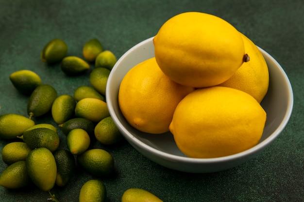 Вид сверху желтых сочных лимонов на миске с кинканами, изолированными на зеленой стене