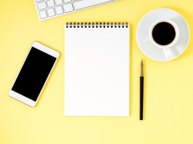 黄色のオフィスデスクトップのメモ帳、コンピューターのキーボード、スマートフォンの平面図。 、 空の