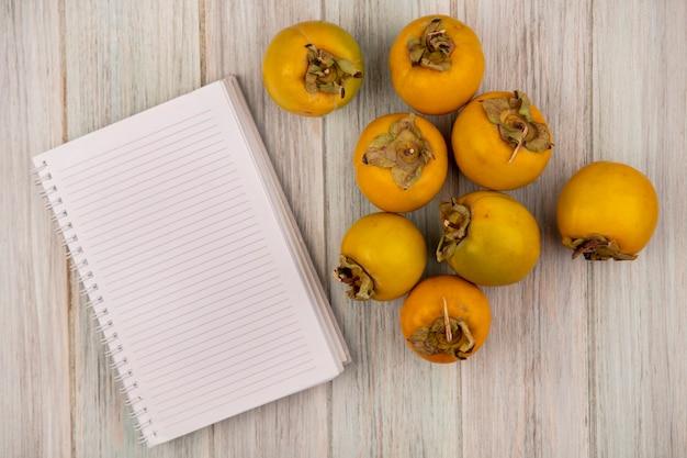 복사 공간이 회색 나무 테이블에 고립 된 노란색 감 과일의 상위 뷰