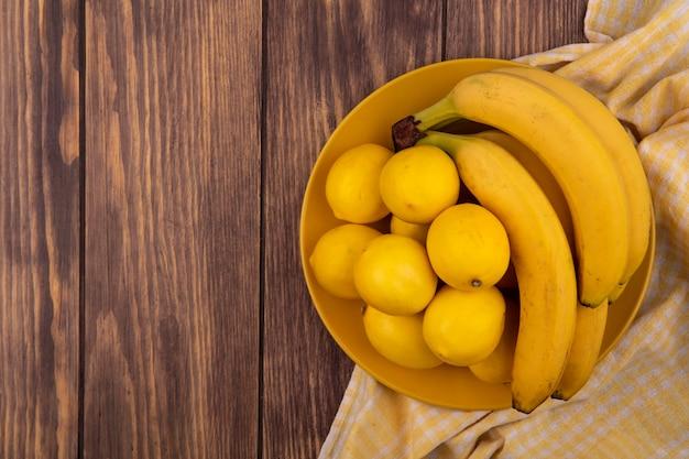 コピースペースのある木製の表面にバナナと黄色のチェックの布の上の黄色のプレート上の黄色の皮を剥がれたレモンの上面図