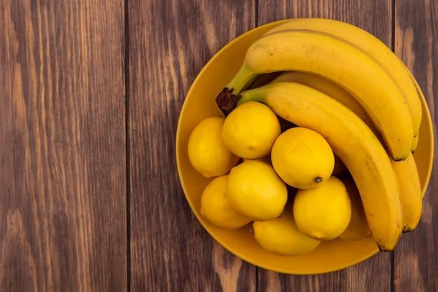コピースペースのある木の表面にバナナが付いた黄色いプレート上の黄色い皮のレモンの上面図