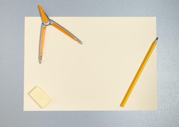 Вид сверху желтых инструментов для рисования. карандаш, циркуль, ластик и лист бумаги на серой поверхности