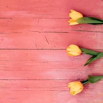 木製の床に黄色のチューリップの花のトップビュー