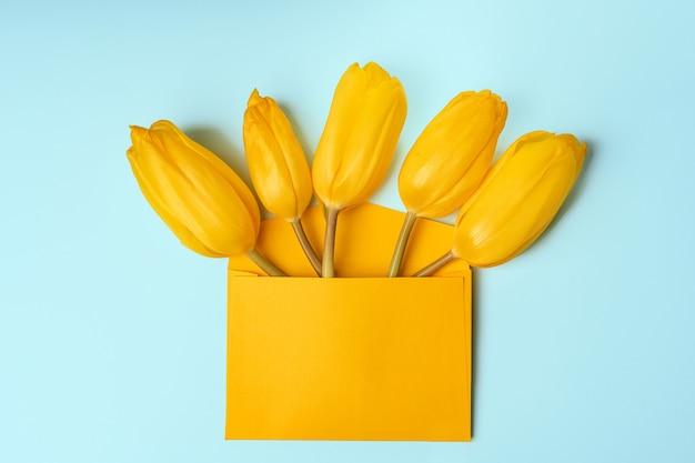 青い背景の上の封筒の黄色いチューリップの上面図。バレンタインまたは春のモックアップ