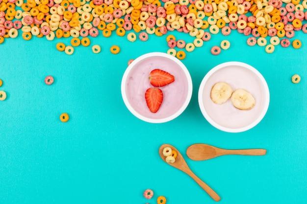 Вид сверху йогурта с йогуртом на синей горизонтальной поверхности