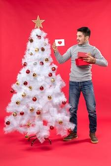 Вид сверху на молодого человека в серой блузке, стоящего возле украшенной белой елки и держащего подарки на красном
