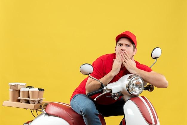 赤いブラウスと帽子を身に着けている若い大人の平面図黄色の背景に驚きを感じて注文を配信