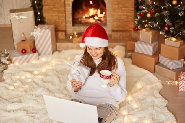 노트북을 들고 바닥에 앉아 행복한 표정을 짓고, 화상 통화를 하는 동안 머그에서 차를 마시고, 웹 카메라에 선물 상자를 보여주는 젊은 성인 여성의 최고 전망.