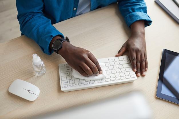 Вид сверху на молодого афроамериканца, протирающего клавиатуру дезинфицирующими салфетками, работая за столом в офисе после пандемии