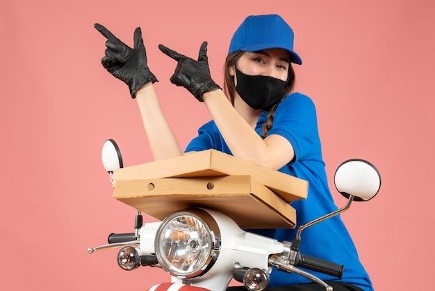 パステル ピーチのボックスを保持している医療マスクと手袋を身に着けている若い野心的な女性宅配便のトップ ビュー