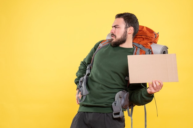 黄色に書かずにシートを保持しているバックパックを持つ若い怒っている旅行男のトップ ビュー