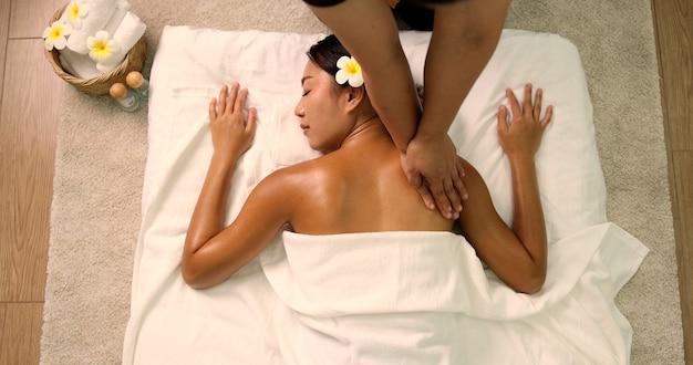 Вид сверху молодой азиатской женщины, получающей масляный массаж на спине в спа-салоне профессиональной массажисткой