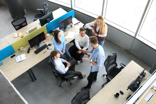 オフィスで握手する若いビジネスパートナーの上面図。握手に焦点を当てます。