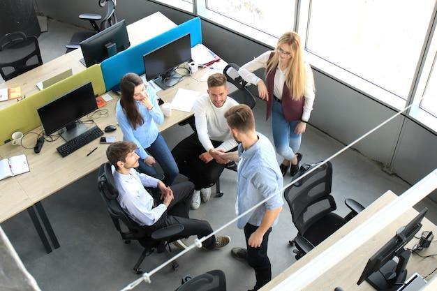 Вид сверху молодых деловых партнеров, пожимая руки по сделке в офисе. сосредоточьтесь на рукопожатии.