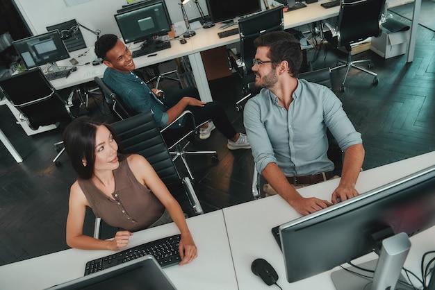 Вид сверху молодых деловых людей, работающих на компьютерах и разговаривающих друг с другом в то время как