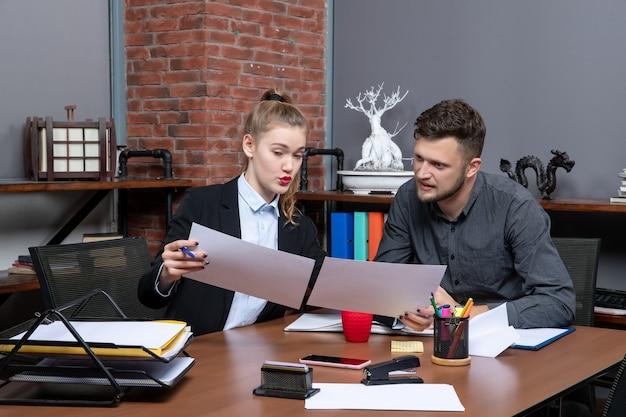 オフィスの文書で1つの問題を議論している若い忙しくてやる気のある事務員の上面図