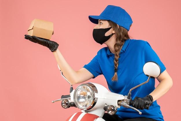 医療マスクとパステル ピーチのボックスを保持している手袋を身に着けている若い集中女性宅配便のトップ ビュー