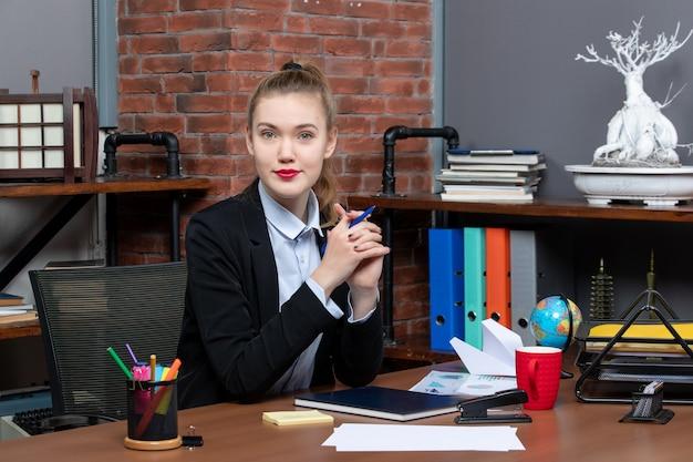 그녀의 책상에 앉아 카메라를 위해 포즈를 취하는 젊은 자신감 여성 회사원의 상위 뷰