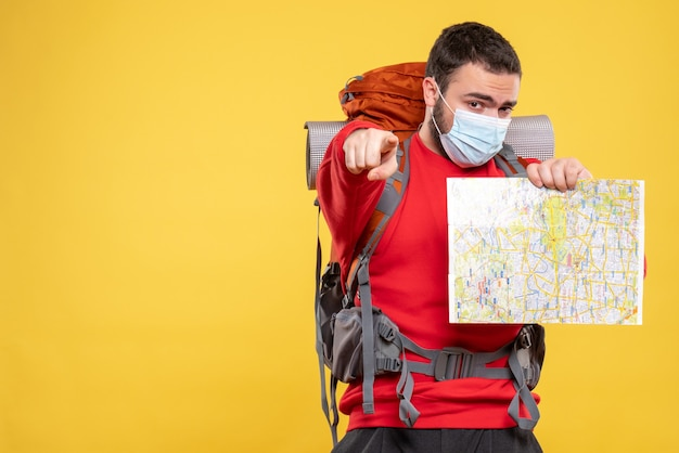 노란색에 앞으로 가리키는지도 들고 배낭과 의료 마스크를 착용하는 젊은 자신감 여행자 남자의 상위 뷰