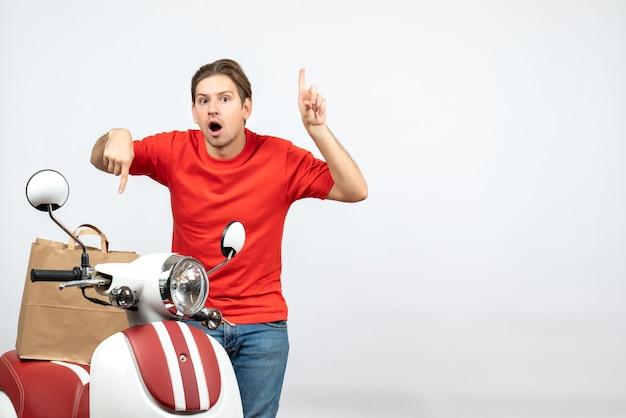 白い壁のスクーターの近くに立っている赤い制服を着て親指を上下に混乱している若い配達人の上面図