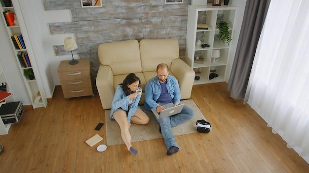 リビングルームのカーペットの上に座ってラップトップでオンラインショッピングをしている若いカップルの上面図。