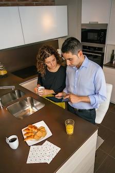 仕事に行く前に家で速いコーヒーを飲みながら電子タブレットを探している若いカップルの上面図