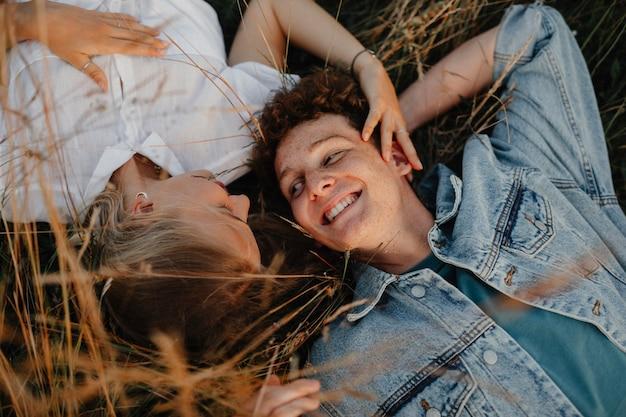 長い草の中に横たわって、田舎の自然の中を散歩している若いカップルの平面図です。