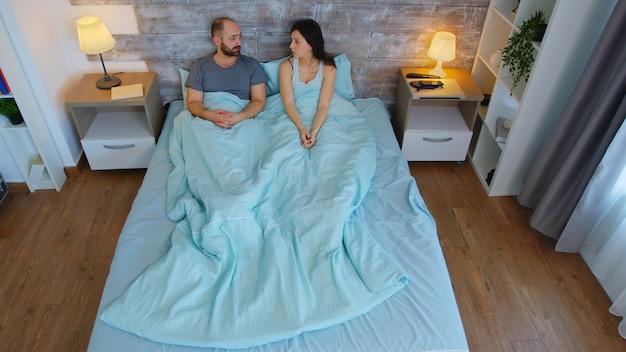 会話をしている朝のベッドシーツの下の若いカップルの上面図。