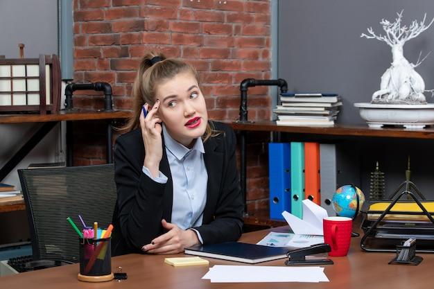 그녀의 책상에 앉아 카메라를 위해 포즈를 취하는 젊은 지친 여성 회사원의 상위 뷰