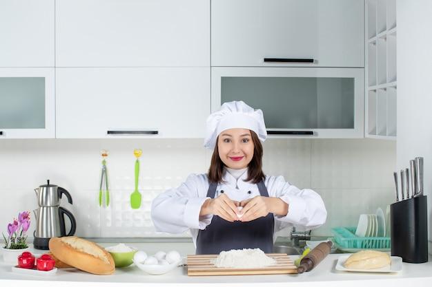 白いキッチンで卵を食べ物に割ってテーブルの後ろに立っている制服を着た若い女性シェフの上面図