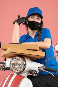 Вид сверху молодой женщины-курьера в медицинской маске и перчатках, держащей коробки, глубоко думая о пастельных персиках