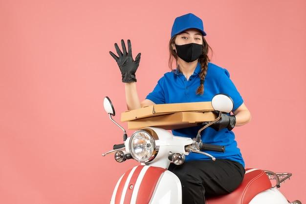 医療用マスクと手袋を着た若い女性の宅配便業者がスクーターに座って、パステルピーチに5つの注文を届けるトップビュー