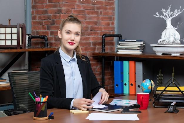 그녀의 책상에 앉아 카메라를 위해 포즈를 취하는 젊은 여성 회사원의 상위 뷰