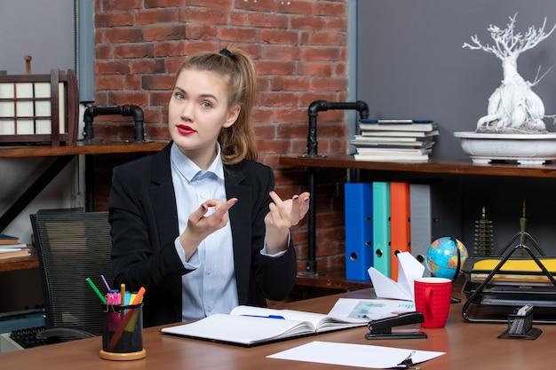 테이블에 앉아 사무실에서 뭔가에 대해 호기심을 느끼는 젊은 여성의 상위 뷰