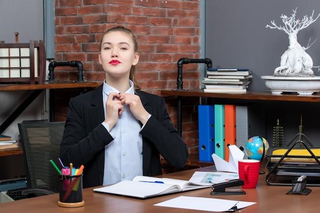 테이블에 앉아 사무실에서 무언가에 집중하는 젊은 여성의 상위 뷰