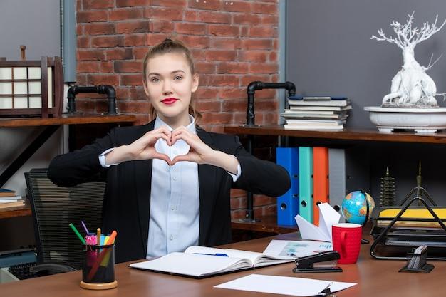 Вид сверху молодой женщины, сидящей за столом и делающей сердечный жест в офисе