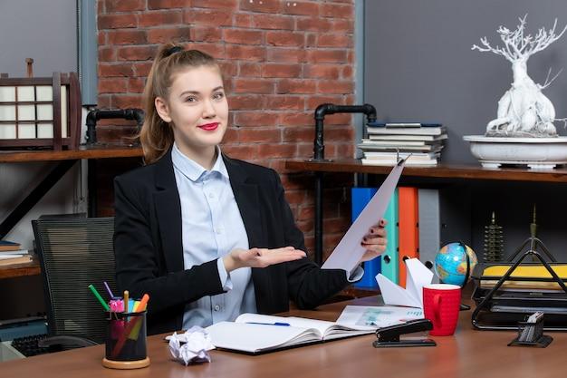 테이블에 앉아 사무실에서 문서를 보여주는 젊은 여성의 상위 뷰