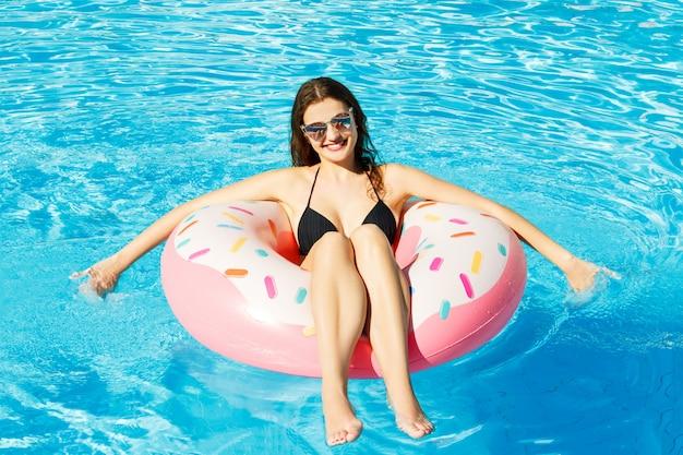 プールでピンクの丸で泳ぐ若い女性のトップビュー