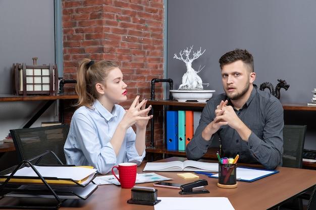 사무실 환경에서 한 가지 중요한 문제를 논의하는 테이블에 앉아 있는 젊은 여성 근로자와 그녀의 남성 동료의 상위 뷰