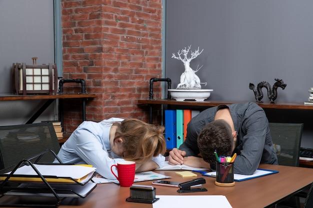 사무실 환경에서 피곤함을 느끼는 테이블에 앉아 있는 젊은 여성 근로자와 그녀의 남성 동료의 상위 뷰