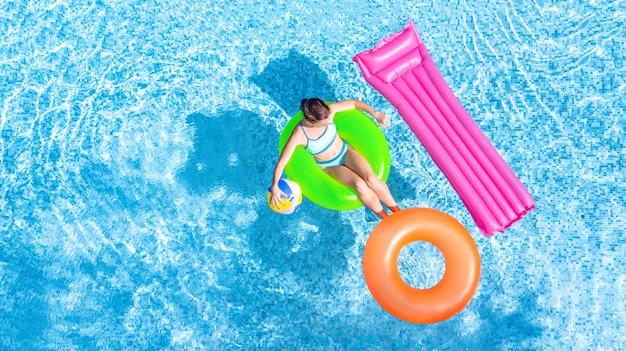 Вид сверху молодой девушки в зеленом надувном кольце рядом с розовым и оранжевым в бассейне